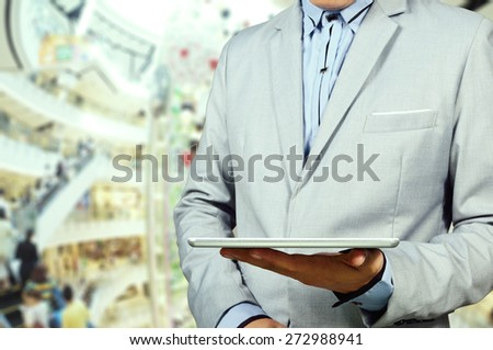 Handsome young man in shopping mall using mobile Tablet PC. Selective focus on Table and Hand. Double Exposure applied. - stock photo