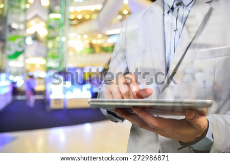 Handsome Young Man in Shopping Mall using Mobile Tablet. Selective focus on Tablet. Double Exposure applied. - stock photo