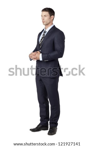 Handsome young man in suit patiently standing with his hands together - stock photo