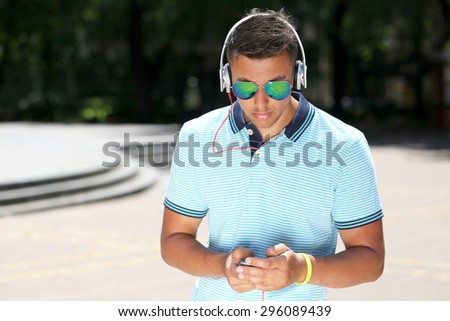 handsome young man in sunglasses listening to music in the city - stock photo