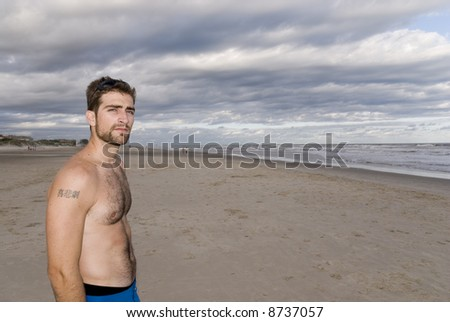 Handsome young man in the sand (late afternoon), with cloudy sky. - stock photo