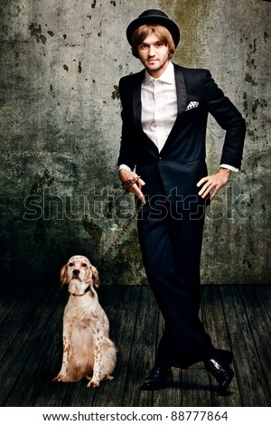 handsome  young  man in tuxedo and his dog in  grunge room - stock photo