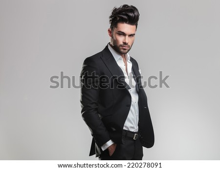 Handsome young man in tuxedo holding his hands in pocket while looking at the camera, on grey background - stock photo