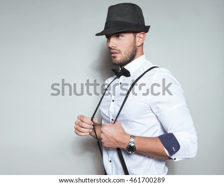 handsome young man in wearing hat, suspenders, bow tie and watch