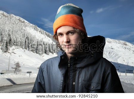Handsome young man in winter clothes and mountains in the background - stock photo