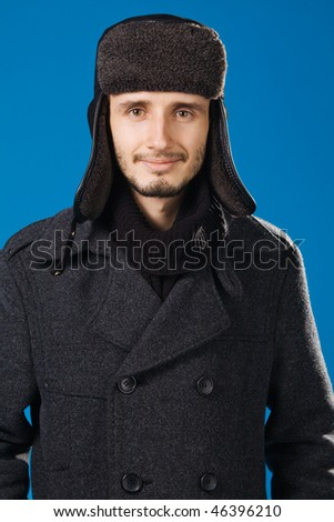 Handsome young man in winter clothing, blue background