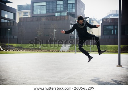 Handsome young man in winter fashion jumping for joy midair on an outdoor urban court surrounded by buildings - stock photo