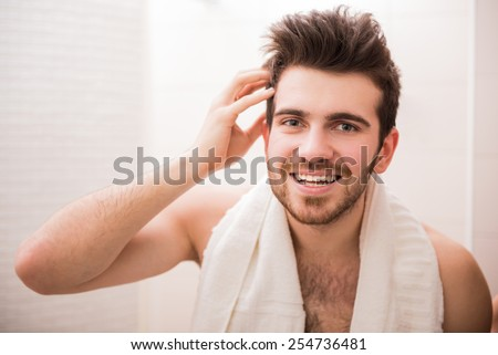 Handsome young man is looking at the mirror and smiling. - stock photo