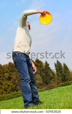 Handsome young man is playing Frisbee - stock photo