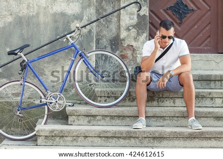 Handsome young man is sitting on the stairs of a building in an old town and talking on the phone while his bicycle is leaned against a wall beside him. - stock photo