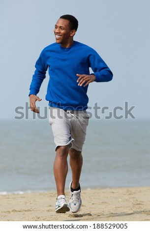 Handsome young man jogging outdoors at the beach  - stock photo