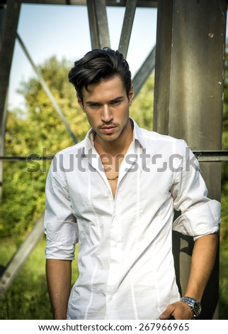 Handsome young man leaning against metal electricity trellis wearing white shirt, looking down - stock photo