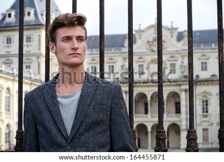 Handsome young man leaning on gate outside elegant palace - stock photo