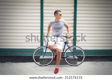 Handsome young man leaning on his bicycle and looking away