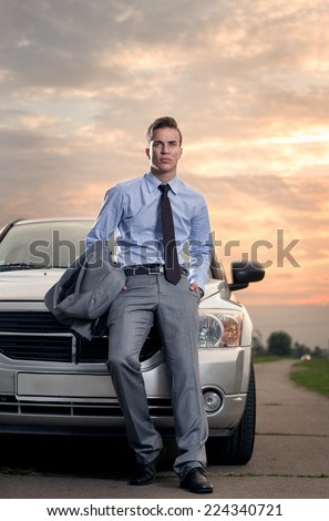 Handsome young man leaning on his car. Attractive gorgeous guy standing, outdoors - outside - stock photo