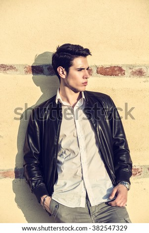 Handsome young man leaning on old wall - stock photo