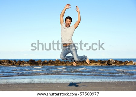 Handsome Young man leaping in air at beach, blue sky and ocean in background - stock photo