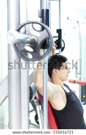 Handsome young man lifting heavy weights at the gym - stock photo