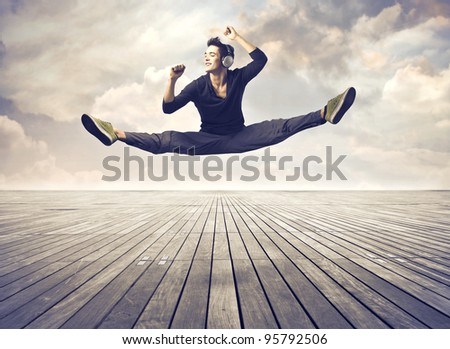 Handsome young man listening to music and dancing on a parquet floor - stock photo