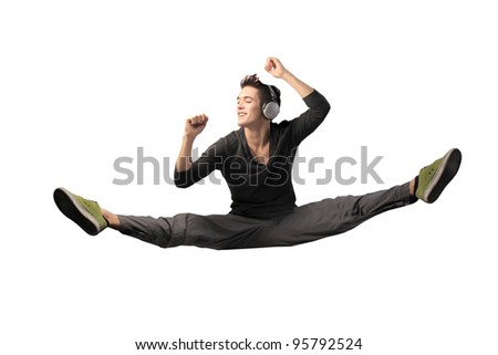 Handsome young man listening to music and jumping - stock photo