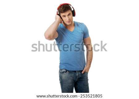 Handsome young man listening to music with headphones.