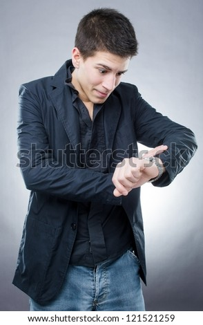Handsome young man looking at his watch like he is late somewhere - stock photo