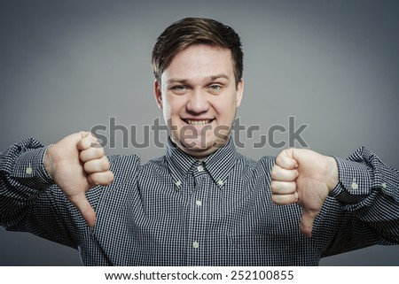 Handsome young man lowered his fist with the thumb down. Close portrait. disgruntled gesture - stock photo