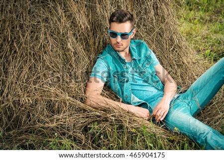 Handsome young man lying in haystack. Male fashion. Denim style.