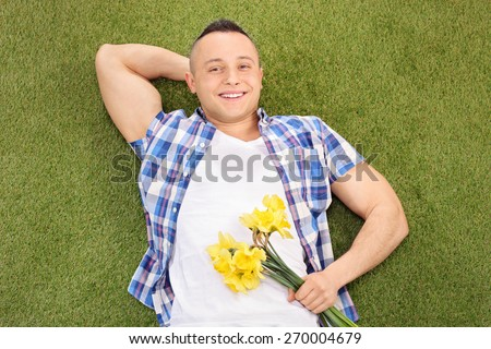 Handsome young man lying on green grass and holding a bunch of flowers - stock photo