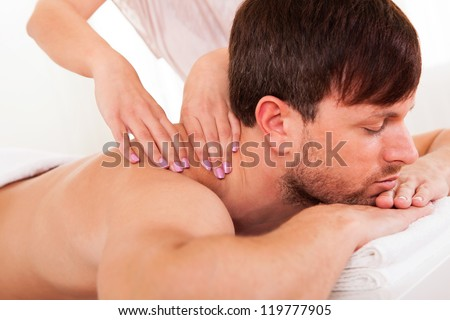 Handsome young man lying on his stomach in a spa having a shoulder massage - stock photo