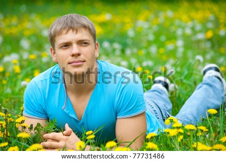 Handsome young man lying on the grass - stock photo