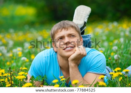 Handsome young man lying on the grass and smiling - stock photo
