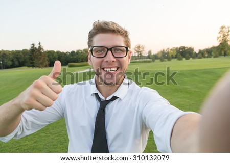 Handsome young man making a selfie picture with smart phone. Blond man showing okay sign and white teeth. He is communicating with foreign friends.  - stock photo