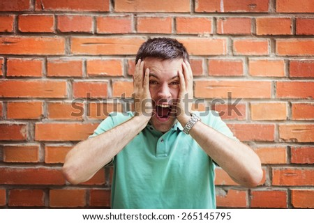 Handsome young man making funny faces on a brick wall background - stock photo