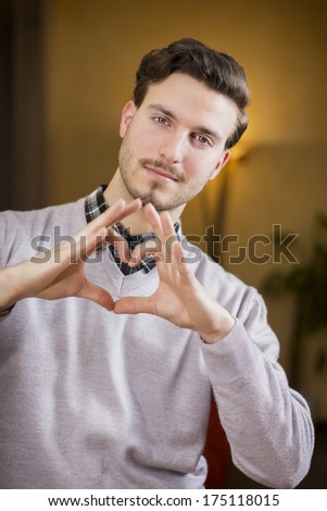 Handsome young man making heart sign with hands, a heart with his fingers - stock photo