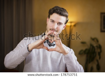 Handsome young man making heart sign with his hands and fingers. Indoors shot inside a house - stock photo
