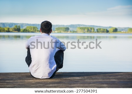 Handsome young man on a lake in a sunny, peaceful day, sitting on a wood pier, thinking or meditating - stock photo