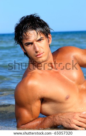 Handsome young man on beach. - stock photo