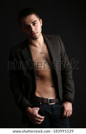 Handsome young man on dark background - stock photo