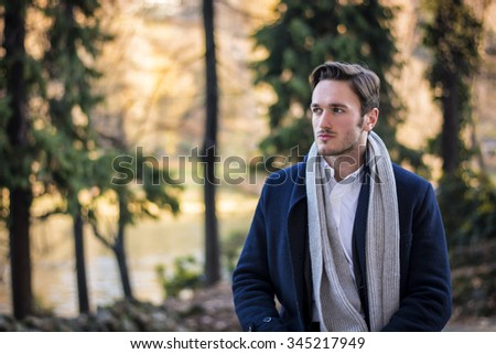 Handsome young man outdoor in winter fashion, wearing black coat and woolen scarf in city park - stock photo