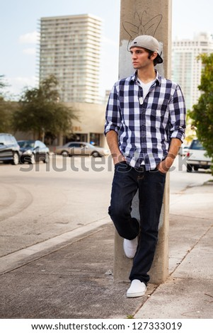 Handsome young man outdoors in a downtown urban setting. - stock photo