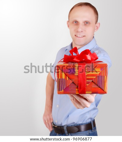 Handsome young man outstret?hed hand with gift box