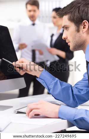 Handsome young man participating at training course. couple standing on background with man pointing to screen on foreground - stock photo