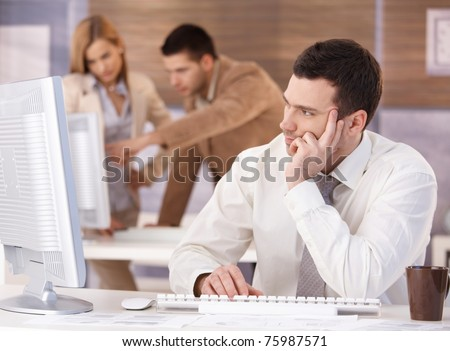 Handsome young man participating at training course, using computer.? - stock photo