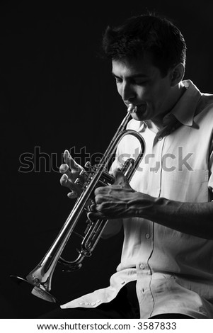 Handsome young man playing a trumpet on black background in black and white