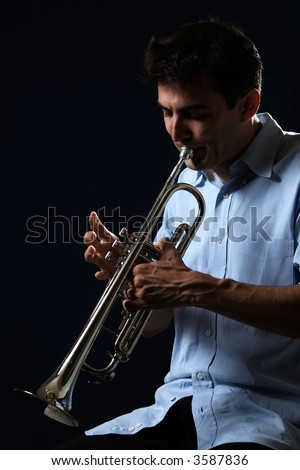 Handsome young man playing a trumpet wearing blue shirt on black background