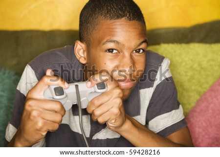 Handsome young man Playing a Video Game with Handheld Controller - stock photo