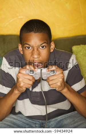 Handsome young man Playing a Video Game with Handheld Controllers - stock photo
