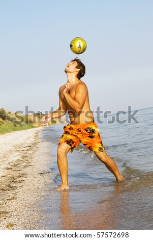 Handsome young man playing football on a sea shore