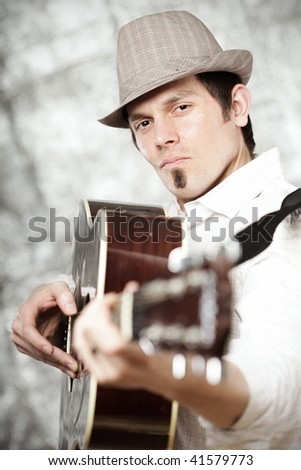 Handsome young man playing his guitar - stock photo